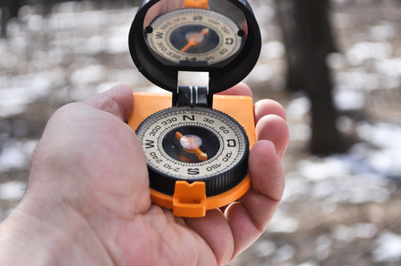 tripping: Magnetic compass in the black case on an orange ground with mirror cover to be in the hands of man.