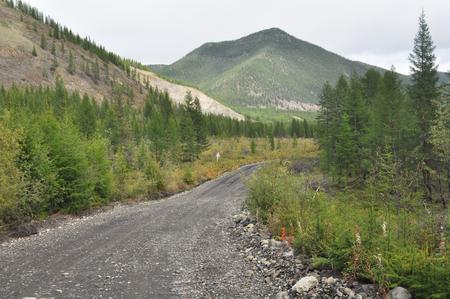 non urban: Soil highway in Yakutia. Cloudy landscape on a route Yakutsk - Magadan. Russia. mountains