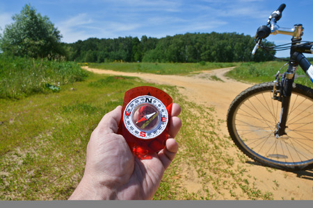 forked road: With a compass and a Bicycle front fork. Orientation during a bike ride in rural areas.