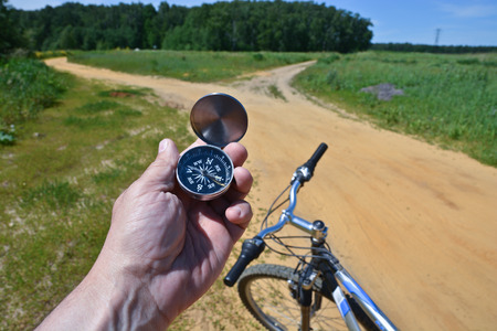outdoor activities: The hand of a man holding a magnetic compass on the background of the Bicycle wheel and summer trails outside of town.
