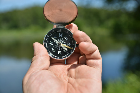 contrary: Mans hand holding compass on the contrary refocusing summer landscape.