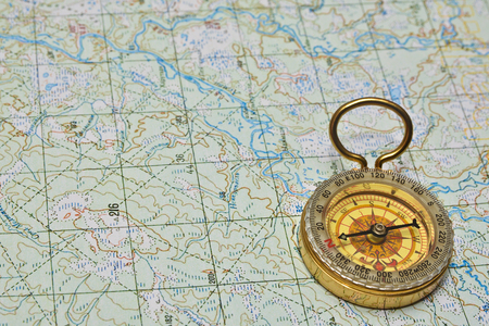 azimuth: Compass and map. The magnetic compass is lying on a topographical map.