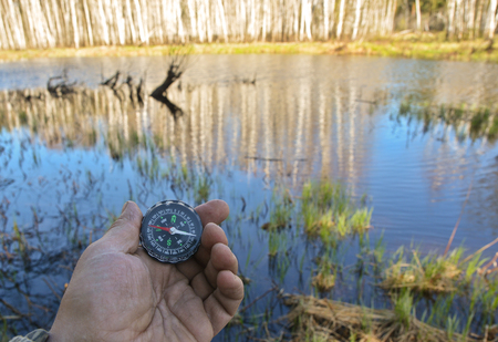 astray: With compass on the walk. A hand holding a magnetic compass on nature background.