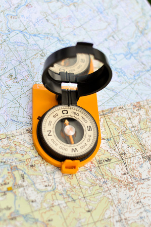topographic: Compass on the map. Magnetic compass in the expanded form is situated on a topographic map. Stock Photo