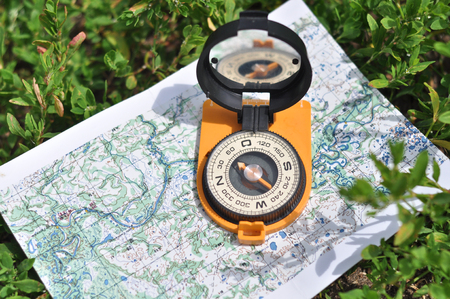 azimuth: Compass on the map. Magnetic compass in the expanded form is situated on a topographic map. Stock Photo