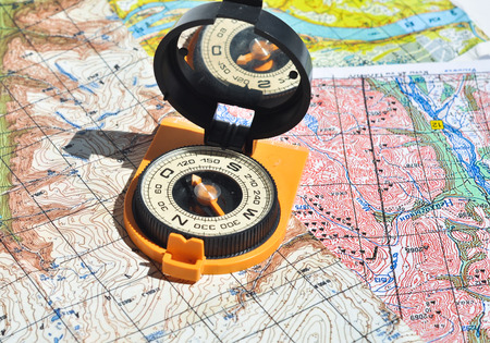 azimuth: Compass and  maps. Compass on the map - this is the open door to the country adventure. Stock Photo