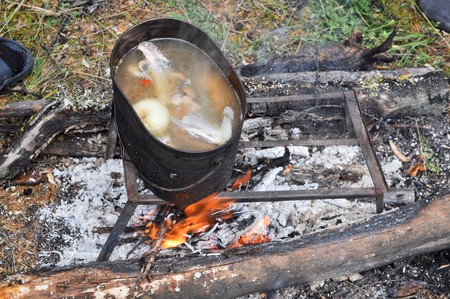 fish fire: Pot on a stand standing over the fire. Preparing fish soup on the fire during the trip.