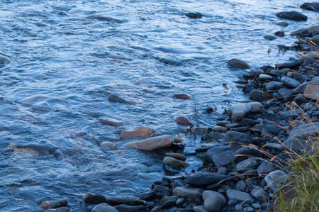 uncultivated: Stones on the shore. The water stream is stroking stones and underlines their color and texture.