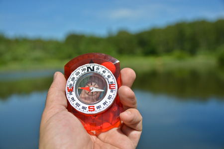 astray: Compass in hand. Magnetic compass is in the hand of the person on a background summer landscape.