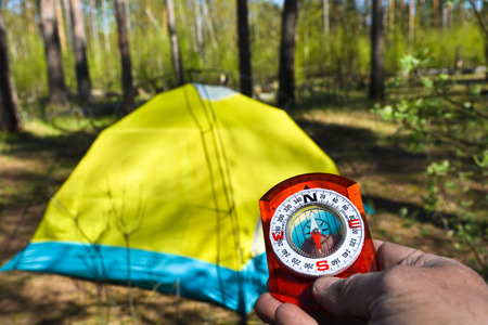 handed: Photo magnetic compass in the hand on the background of wild nature. Stock Photo