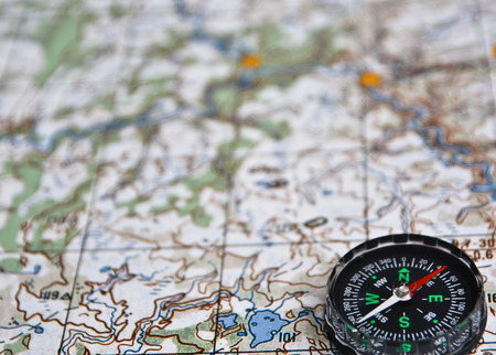 azimuth: The magnetic compass is located on a topographic map. Satellites adventure - map and compass.