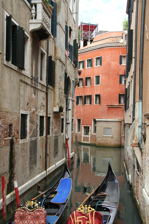 gaily: Venetian landscape with gondolas. Canal in Venice with gaily decorated gondolas moored to the berth.