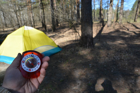 orienteering: Orienteering in the woods with a compass. Compass in hand on background of tourist tents.