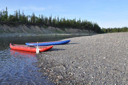 riverside county: Inflatable kayaks on the shore taiga rivers. The river of the polar Urals in the Republic of Komi, Russia. Stock Photo
