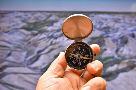 Compass in hand on background of the relief. Mans hand holds a magnetic compass.