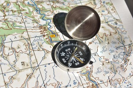 topographic: Map and compass - the tools for navigation. The magnetic compass lies on a topographic map.