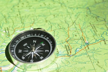 topographic: Dont get lost in the journey! The magnetic compass lies on a topographic map. Stock Photo