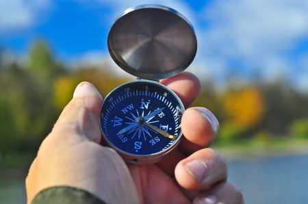 Compass in hand. Magnetic compass in hand on the autumn landscape. Stock Photo