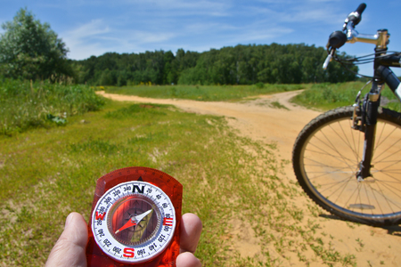 With a compass and a Bicycle front fork. Orientation during a bike ride in rural areas.
