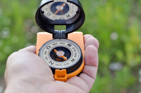 The compass in his hand. Magnetic compass in hand on the green meadows. Stock Photo