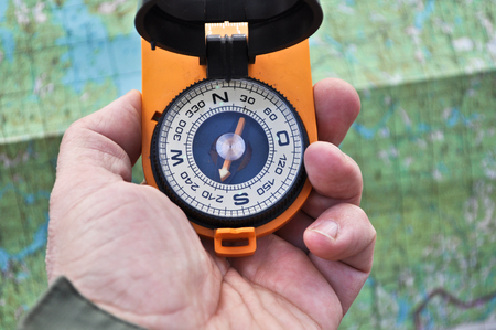 chrome man: Magnetic compass in the black case on an orange ground with mirror cover to be in the hands of man.