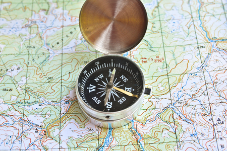 The compass lies on the map. Navigation tools needed for orientation. Stock Photo