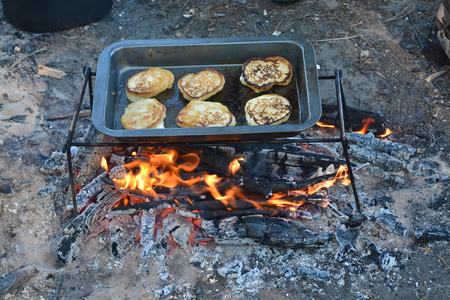 A pan with pancakes on fire. Preparation of breakfast at the stake.
