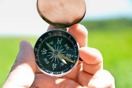Compass in hand. A navigation tool for off-road orientation. Stock Photo