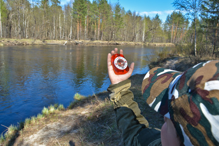 The boy with the compass. The magnetic compass in the hand of the boy on the background of the spring river. Stock Photo