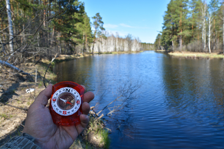With compass on spring river. Magnetic compass in the hand on the background of the river in the national Park.