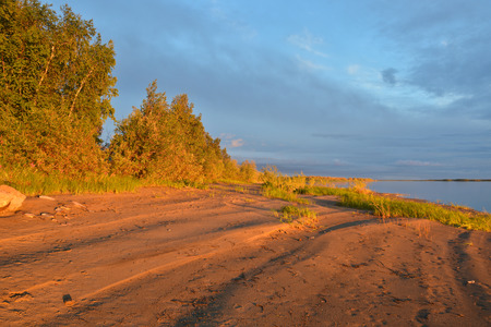 The shore of the northern river, lit by the setting sun. Deserted evening landscape.