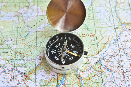 The compass lies on the map. Navigation tools needed for orientation. 写真素材