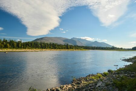 Clouds over Mount Telposiz are reflected in the Schugor River. Yugyd VA National Park in the Northern Urals in Russia. Imagens