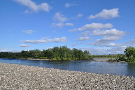 River landscape in the polar Urals. The pebbly shore of the North river Kokpela, Republic of Komi, Russia. Imagens