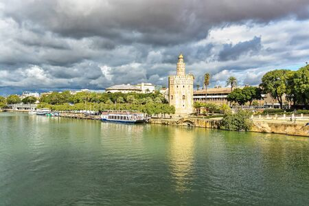 The center of Seville and its symbol, the Golden tower. Urban landscape of the capital of Andalusia, Spain.