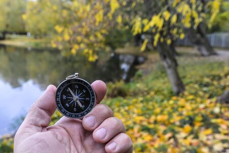 Compass orientation. Compass in hand against the background of nature.