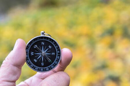 Compass orientation. Compass in hand against the background of nature. Imagens