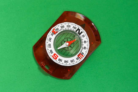 Compass on a green background. Magnetic compass, a tool for navigation.