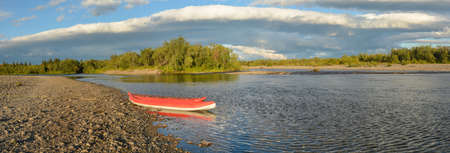 Boats on the Bank of the Northern river, panorama. Travel on inflatable kayaks on the taiga river.