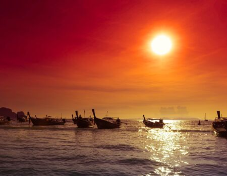 Sea coast landscape nature background, fishing boats silhouettes at evening  Red sunset with warm sun rays and dark ocean water in Asia photo