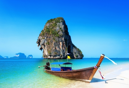 Thailand beach. Beautiful tropical landscape with boat, blue and clear ocean water, white sand and island. Thai journey photography