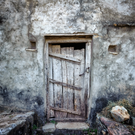 mud house: Grunge old door background texture on vintage retro building wall