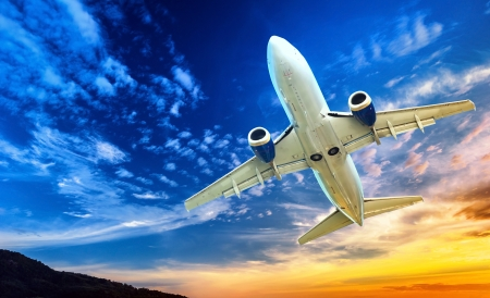 Airplane transportation  Jet air plane flies in blue sky Stok Fotoğraf