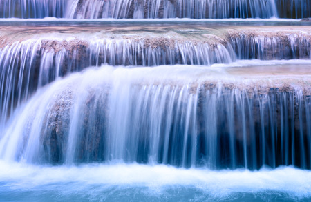 Mountain river background with small waterfalls in tropical forest  Clean blue water flows on cascades of Erawan park in Thailand