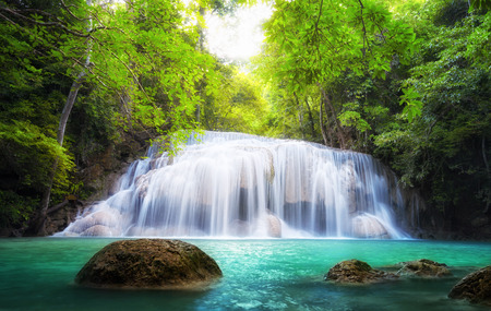 Tropical waterfall in Thailand, nature photography  Fresh water mountain river in wild green jungle forest  Scenic and peaceful Asia nature background of beautiful blue water pool and creek cascade photo