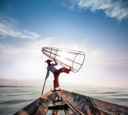 inle: Burma Myanmar Inle lake fisherman on boat catching fish by traditional net  Outdoor photography Editorial