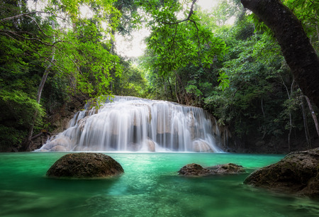 Waterfall in tropical forest. Beautiful nature background. Jungle trees and blue water of mountain river in national park in Thailand, Asia 스톡 콘텐츠