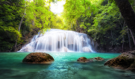 Tropical waterfall in Thailand, nature photography  Fresh water mountain river in wild green jungle forest  Scenic and peaceful Asia nature background of beautiful blue water pool and creek cascade Standard-Bild