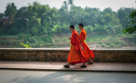 buddhist monk: LUANG PRABANG, LAOS - 8 DEC, 2013: Two unidentified young monks passing the street of city. Luang Prabang is one of most popular tourist destinations in Laos