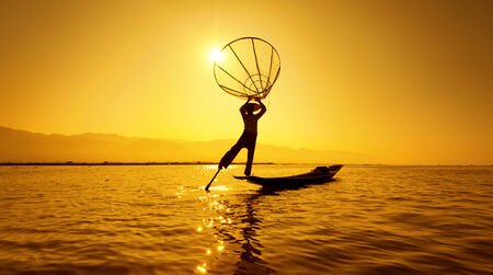 Burma Myanmar Inle lake fisherman on boat catching fish by traditional net  Outdoor sunset photography photo